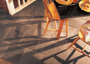 A Vermont Soapstone floor is light blue-gray with subtle veining. The oiled table is nearly black with the light veins in high contrast.