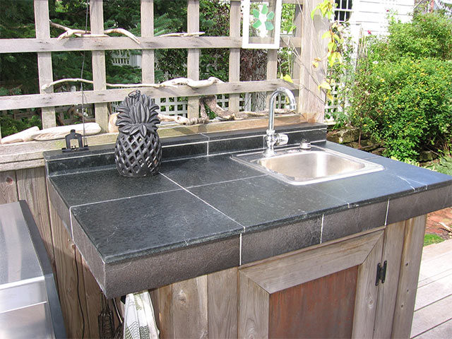 A Vermont Soapstone outdoor sink with both oiled and dry finish.