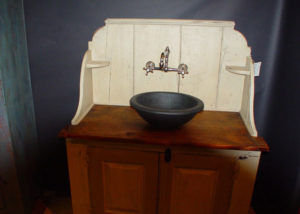 A Vermont Soapstone Cooper sink used as a basin on an antique cupboard makes this unique bathroom vanity one-of-a-kind.