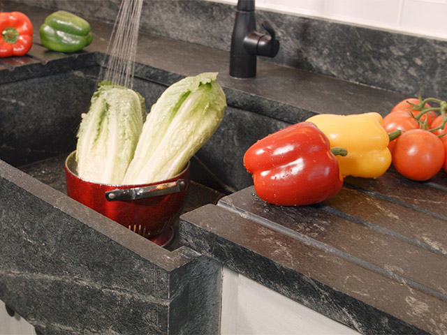 Vermont Soapstone drain board grooves are a permanent part of the kitchen soapstone countertop and slope into the sink.