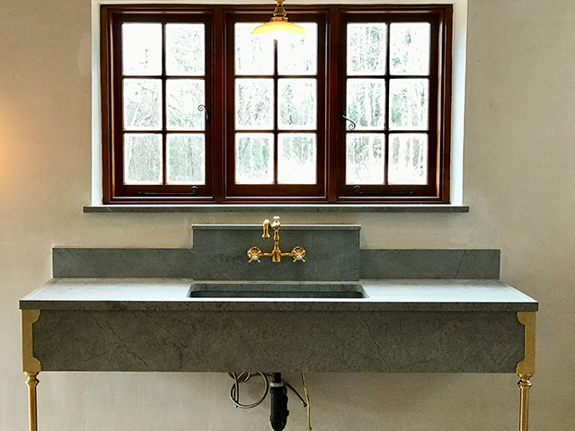 Stunning extra-wide Vermont Soapstone sink with gold accents is the focalpoint of the room.